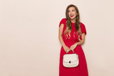 Smiling Beautiful Woman In Red Dress With Beige Purse Is Looking Away And Talking - 239483327