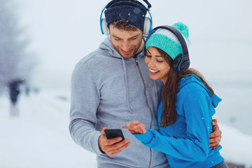 Young sports couple resting after jogging on snowy day in the city