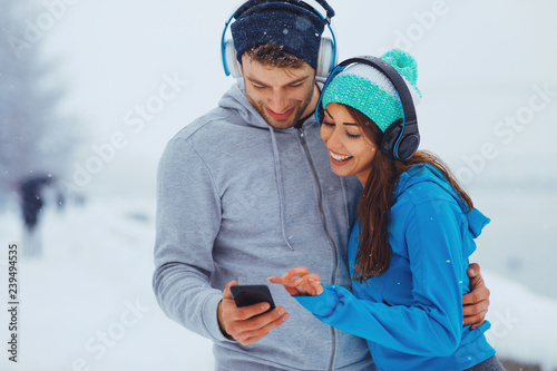 Foto Murales Young sports couple resting after jogging on snowy day in the city