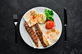 Lamb Kebab. Pita bread and spices. On a black background. Top view. - 239509995
