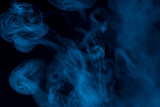 magic patterns formed by blue cigarette smoke close up against a dark background