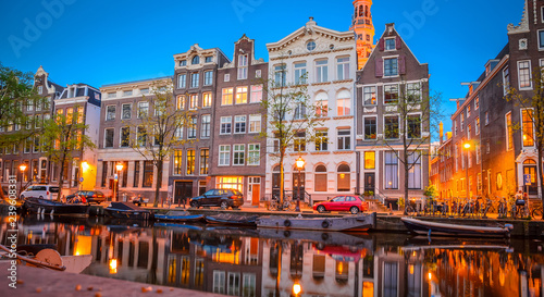 Traditional old buildings and boats at night in Amsterdam, Netherlands.