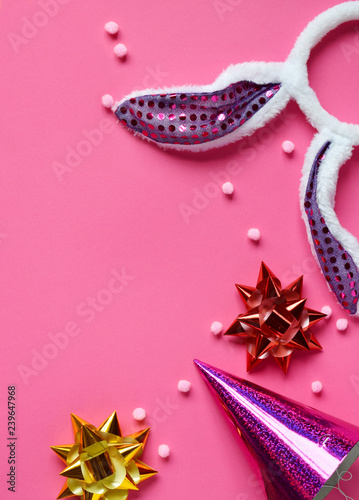 Carnival accessories set on pink background. Birthday or winter party props. Honeycomb balls, hair hoop in shape of rabbit ears. Copy space. Top view - 239647968