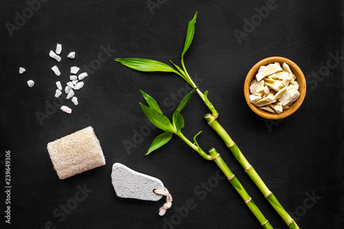 Asian spa background. Spa treatment concept. Bamboo branch, spa cosmetics on black background top view. Foot spa