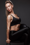 Sports girl with pumped muscles,beauty body in a tracksuit, leading a healthy lifestyle and posing in the studio.