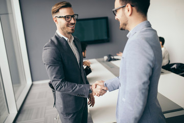 Business people shaking hands, finishing up meeting © nd3000