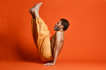Old man practicing yoga doing stretching exercises against orange background © Daria