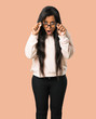 Young afro american woman with glasses and surprised on isolated brown background