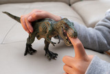 kid playing a tyrannosaurus toy and putting his finger inside the mouth