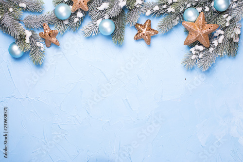 Decorative branches fir tree, golden stars and blue balls on blue textured background.