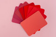 Color swatches sample cards spread in fan shape - hues of red with copy space