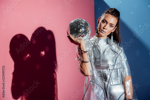 fashionable model in silver bodysuit and raincoat posing with disco ball on pink and blue background