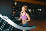 Blond young, motivated woman running on the treadmill in the gy