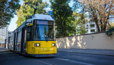 Public transportation concept. Tram yellow, modern, electric at Berlin, Germany. City and nature background.