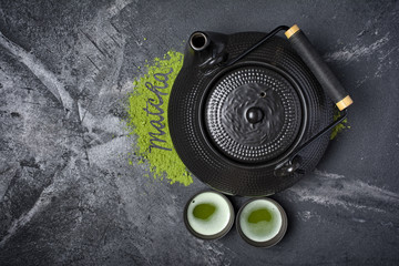 Top view on organic green matcha tea with traditional black asian kettle