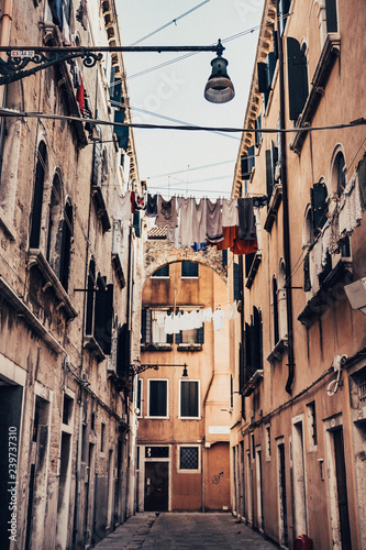 Old street in Venice Italy, with hanging clothes. - 239737310