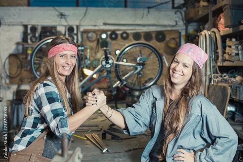 Leinwanddruck Bild two young women posing in a workshop