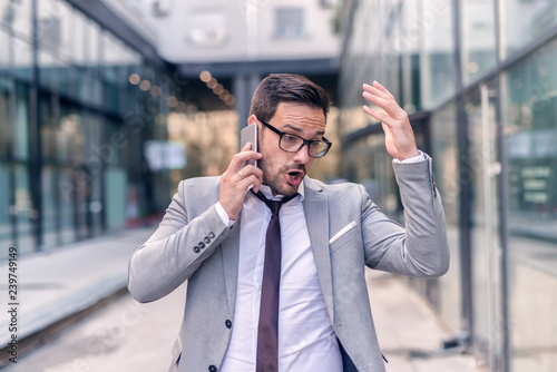 b647eb8e385f Worried businessman dressed in formal wear using smart phone for a business  talk while walking on