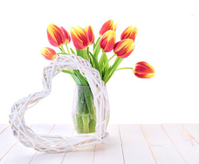 Spring decoration with red tulips and stugged heart on white wooden table