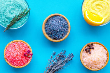 Aromas of bath salt. Lemon, coffee, rosemary, rose, lavender near bowls with colorful bath salt on blue background top view © 9dreamstudio
