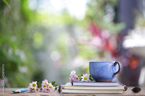 Old blue cup and notebook with flower on wooden table - 239781175