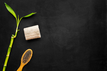 Asian spa treatments with natural ingredients concept. Bamboo branch, spa cosmetics on black background top view copy space