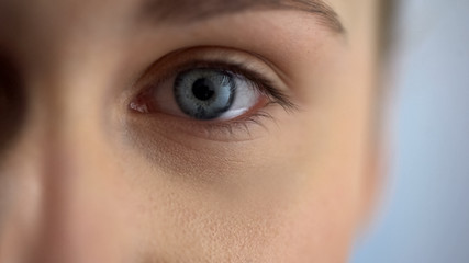 Blue-eyed woman checking eyesight at ophthalmologist in clinic, looks at camera