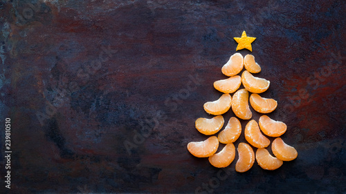 Tangerine christmas tree  on dark rust metal grunge background. Xmas festive greeting card with a tree of orange tangerine slices and star, copy space, flat lay - 239810510