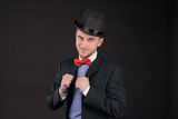 portrait of adult young elegant man in cylinder hat and bowtie on dark background - 239811116