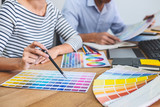 Two colleagues creative graphic designer working on color selection and drawing on graphics tablet at workplace, Color swatch samples chart for selection coloring - 239819942