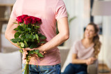 couple, relationships and people concept - happy woman looking at man hiding bunch of roses behind his back