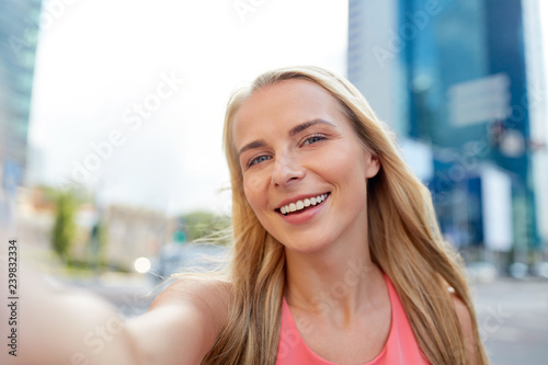 obraz lub plakat lifestyle and people concept - happy young woman taking selfie on city street