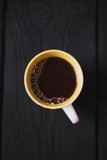 cup of black coffee from above on dark wooden table. caffeine drink. coffee background.
