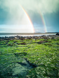 Rainbow above the famous Dinosaur footprints at An Corran beach by Staffin on the isle of Skye