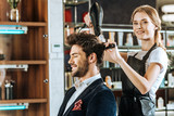beautiful young hairstylist smiling at camera while drying and combing hair to handsome client in beauty salon - 239855170