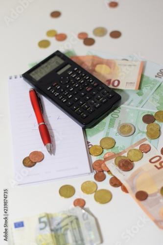 Geldscheine und Münzen, Euros und Centstücke,  mit Taschenrechner, Notizblock und Kugelschreiber auf einem weißen Tisch - 239874735
