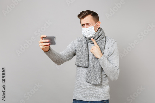 Leinwanddruck Bild Young man in sweater, scarf sterile face mask making video call with mobile phone, pointing index finger on himself isolated on grey background. Health ill sick disease treatment, cold season concept.