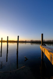 wooden piles sticking out of the water surface at sunrise