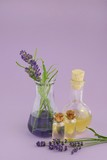 lavender oil set in  bottles and lavender flowers in laboratory flask on a bright lilac background
