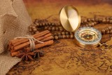 Vintage compass and cinnamon spices on a old world map - trade and explorer concept