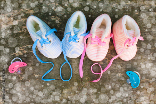 Leinwanddruck Bild      2019 new year written laces of children's shoes and pacifier on old wooden background. Top view. Flat lay.