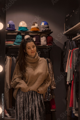 9055b484f2 beautiful brunette girl in a brilliant skirt and a stylish sweater in  hipsters showroom women's clothing