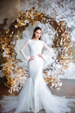 Fashion portrait of beautiful young woman in a gorgeous wedding dress, posing in a fantasy interior with white winter tree