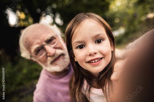 Foto Murales Little girl taking selfie with her grandpa