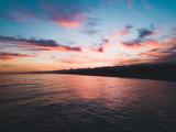 Bellissimo cielo al tramonto infuocato con nuvole arancione e rosso in riva all'oceano calmo. Vista aerea