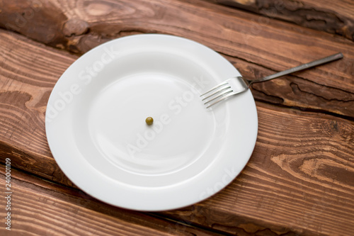 Diet concept. One pea lying on a white plate. Restriction in nutrition. - 240001109