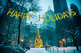 Golden Happy Holidays banner hanging over glowing Christmas tree in a snow-covered park surrounded by skyscrapers