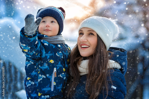 Leinwandbild Motiv Woman and child in winter in nature. Portrait of a happy family