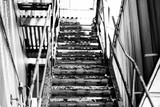 Black and White Fire Escape Stairs Looking Up With Chipped Paint In High Contrast During Day