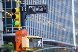 Wall street sign in the foreground and a huge blurred building in the background in Manhattan.